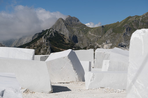 Blocks of white Carrara marble deposited in a square near the quarries. - MyVideoimage.com | Foto stock & Video footage