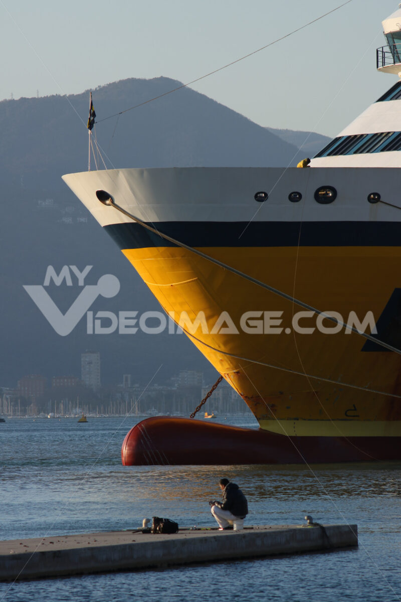 Bow of a yellow ship anchored in port with a fisherman on the dock. -Foto navi. Ships photo.