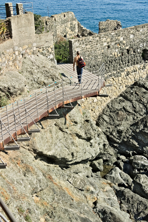Boy walks on a path in Framura, near the Cinque Terre. Walkway o - MyVideimage.com