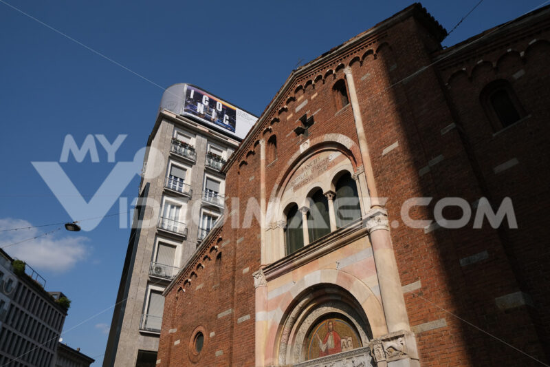 Brick facade of the church of San Babila in Milan. On the facade a mosaic. In the background modern buildings. - MyVideoimage.com