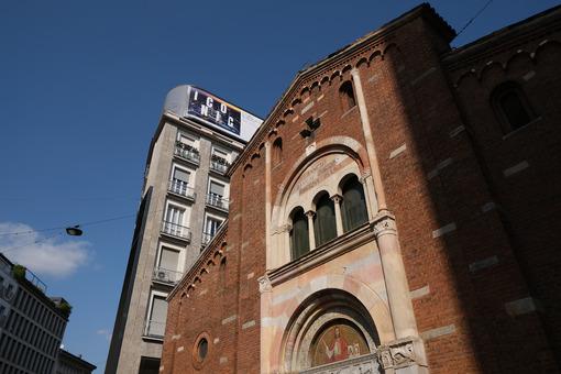 Brick facade of the church of San Babila in Milan. On the facade a mosaic. In the background modern buildings. - MyVideoimage.com
