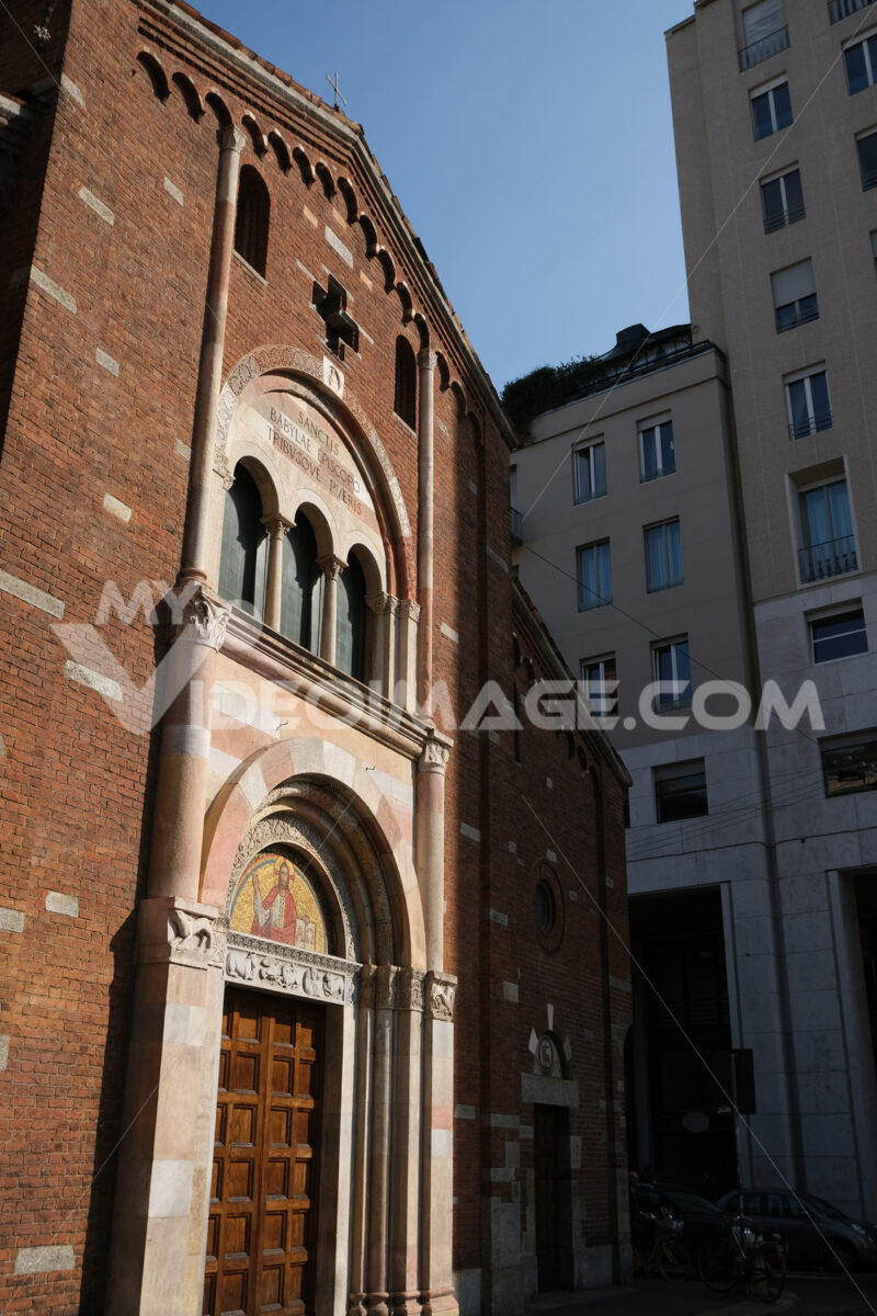Brick facade of the church of San Babila in Milan. On the facade a mosaic. In the background modern buildings. Milano foto. - LEphotoart.com
