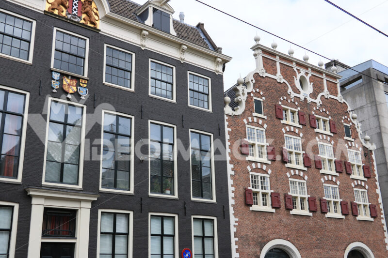 Brick houses in Amsterdam. Typical red and gray brick houses with large white windows. - MyVideoimage.com | Foto stock & Video footage