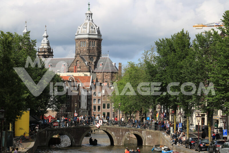 Bridge on a city canal with people walking. In the background an ancient church with a dome and bell tower. - MyVideoimage.com