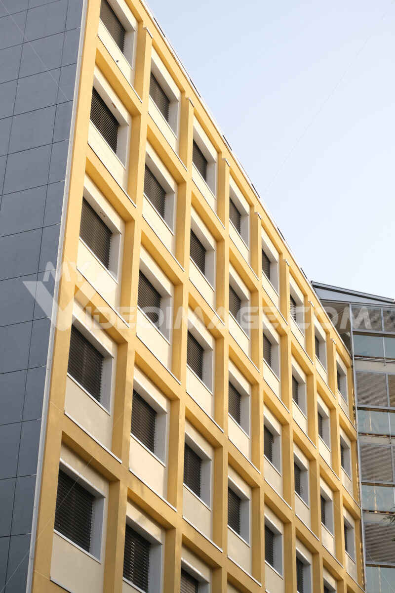 Brutalist building. Building facade with modern period windows and frames. Pillars and beams painted in yellow. - MyVideoimage.com | Foto stock & Video footage