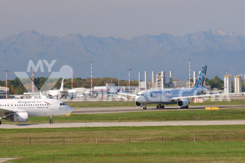 Bulgaria Air Airbus A320-214  airplane on the Malpensa airport runway. In the background the buildings of Terminal 1 and other airplanes. - MyVideoimage.com