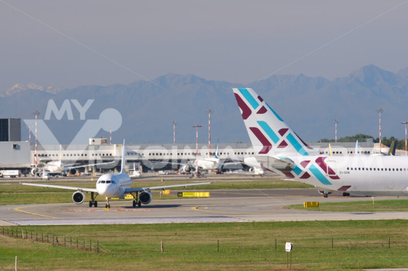 Bulgaria Air Airbus A320-214 airplane on the Malpensa airport runway. In the background the buildings of Terminal 1 and parked airplanes. - MyVideoimage.com