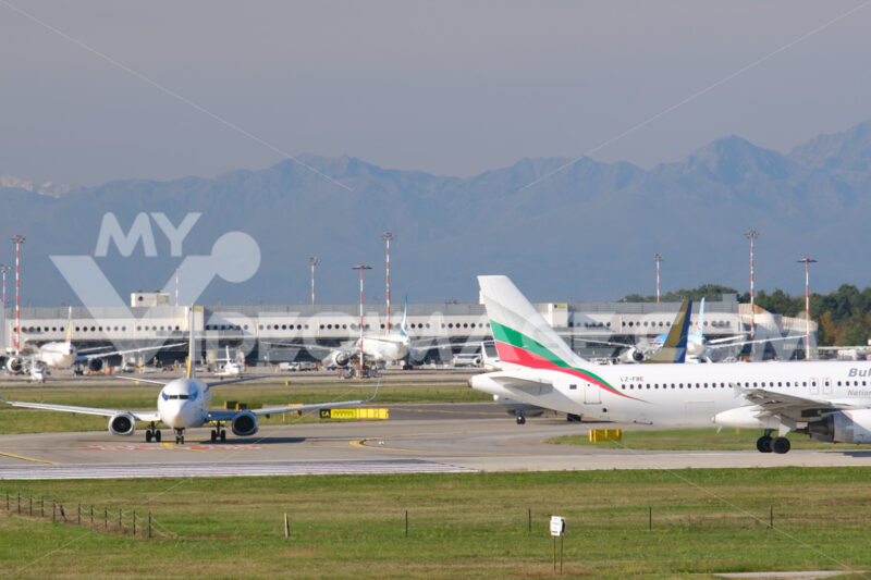 Bulgaria Air Embraer 190/195 airplane on the Malpensa airport runway. In the background the buildings of Terminal 1 and parked airplanes. - MyVideoimage.com