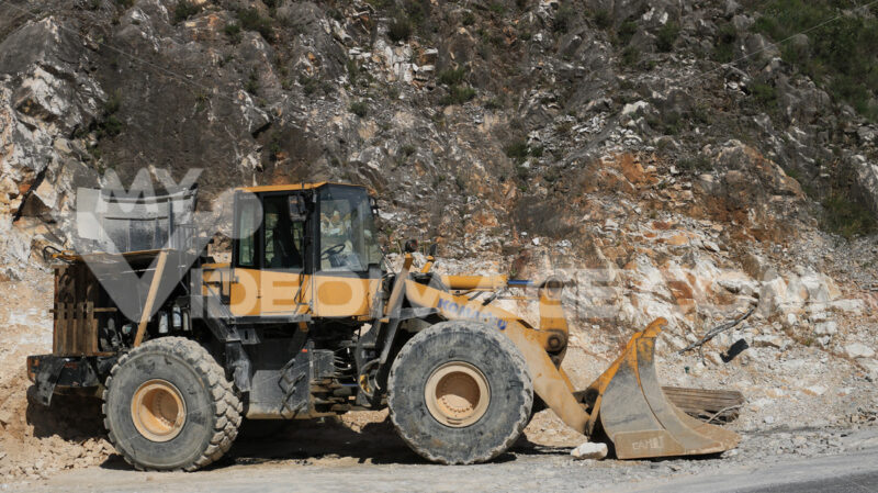 Bulldozer in a Carrara marble quarry. A large Komatsu mechanical - MyVideoimage.com