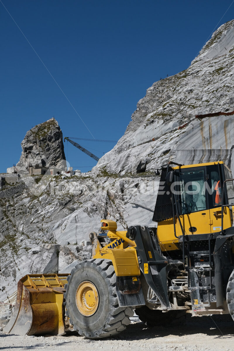 Bulldozer. Large white marble quarry with blue sky background. - MyVideoimage.com | Foto stock & Video footage