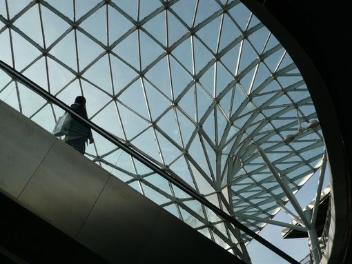 Businessman waiting inside a pavilion of the Milan fair. Modern architecture with steel and glass lattice structure. - MyVideoimage.com