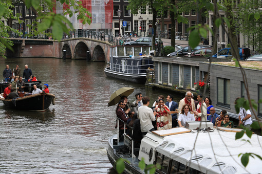 Canal party. A family celebrates on the boat in the city center. - MyVideoimage.com