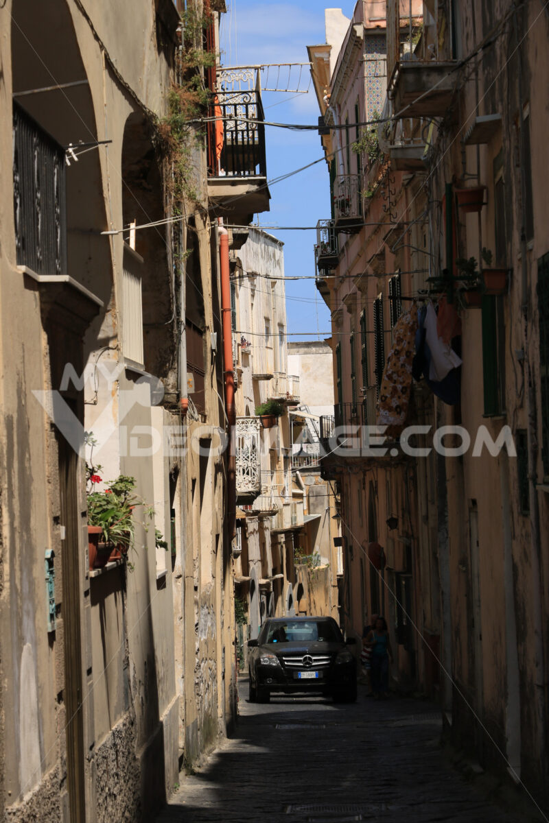 Car in narrow street. Narrow and old road on the Island of Procida. A luxury car passe - MyVideoimage.com | Foto stock & Video footage