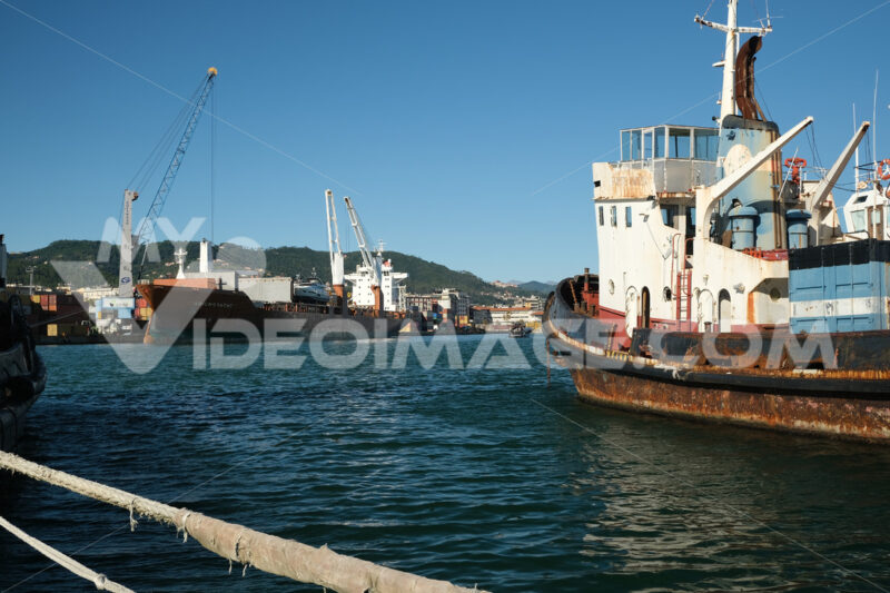 Cargo ship loading at the port of La Spezia. In the foreground an old ship cart of the sea. Foto navi. Ships photo.