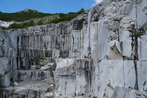 Cava di marmo sulle Alpi Apuane. Wall of a white marble quarry under the mountain. Foto stock royalty free. - MyVideoimage.com | Foto stock & Video footage