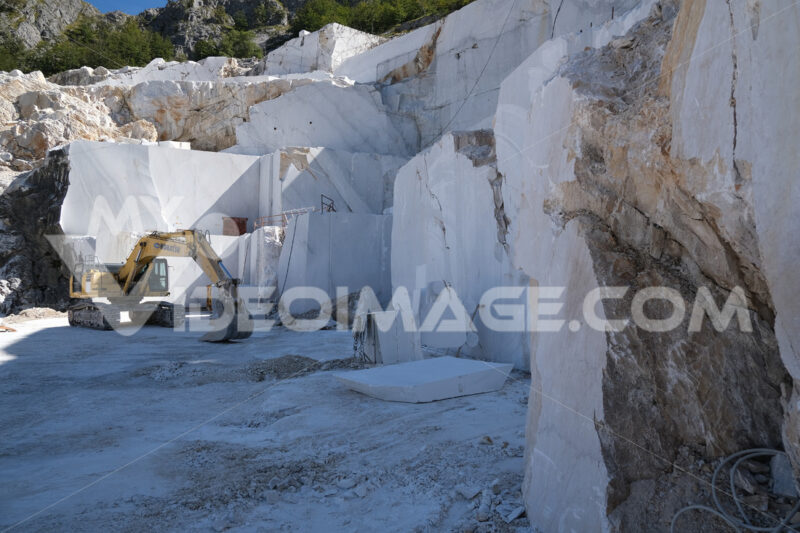 Cave di marmo con escavatore Komatsu. Crawler excavator in a marble quarry near Carrara. Foto stock royalty free. - MyVideoimage.com | Foto stock & Video footage