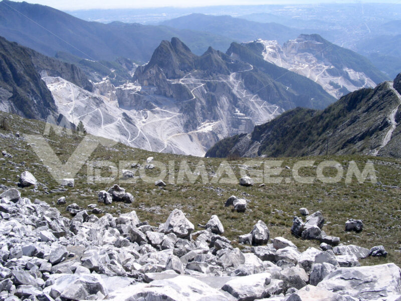 Cave marmo. Alpi Apuane and Carrara Marble Quarries. Extraction of Carrara marble from the mountains. In the background the sea. - MyVideoimage.com | Foto stock & Video footage