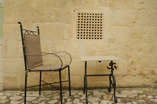 Chair with iron table in a courtyard in the city of Matera. Beige stone wall with marble air grilles. - MyVideoimage.com