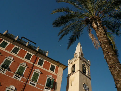Chiesa Lerici La Spezia. Palace and bell tower of the church of Lerici with a blue sky background and a palm tree in the foreground. - MyVideoimage.com | Foto stock & Video footage