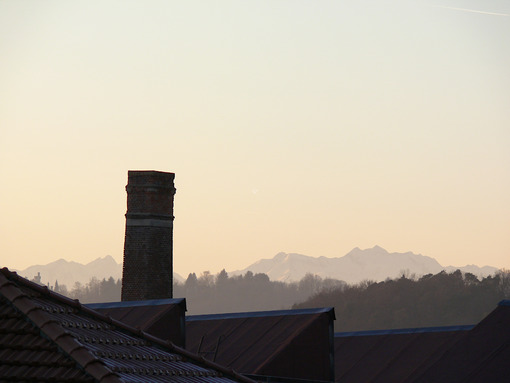 Chimney of old abandoned industrial complex. Work of industrial archaeology. In the background the profile of the mountains (Alps) - MyVideoimage.com