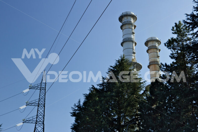 Chimneys and electric pylons behind treesTurbigo. - MyVideoimage.com
