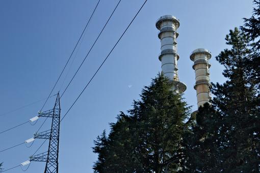 Chimneys and electric pylons behind treesTurbigo. - MyVideoimage.com