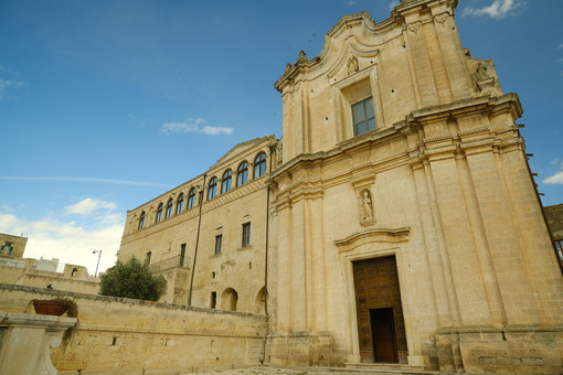Church and Convent of Sant'Agostino in Matera. Courtyard with olive trees with leaves moving in the wind. - MyVideoimage.com | Foto stock & Video footage