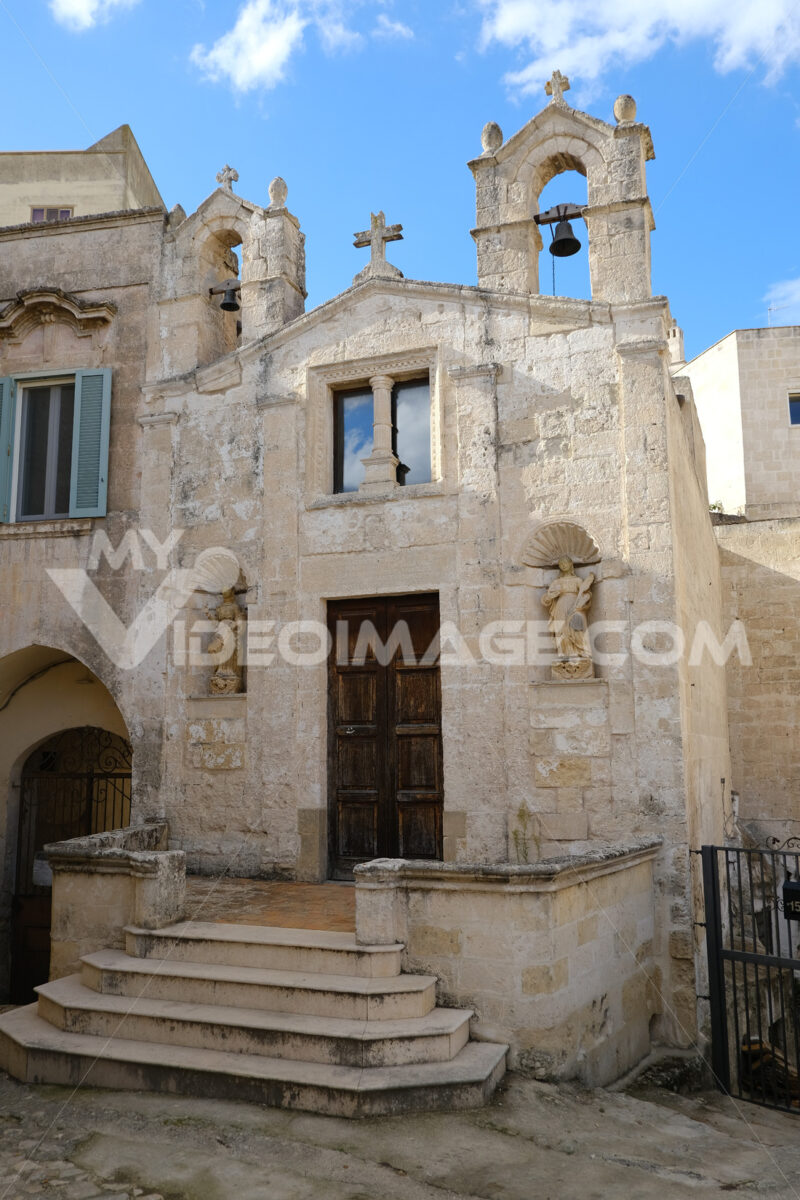 Church of San Biagio in Matera located in the Foggiali area. The construction is made of blocks of tufa stone of beige color. Facade with two small bells. - LEphotoart.com
