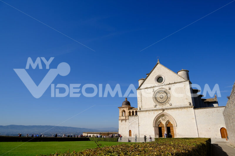 Church of San Francesco in Assisi with the stone wall. The basilica built in Gothic style houses the frescoes by Giotto and Cimabue. - MyVideoimage.com