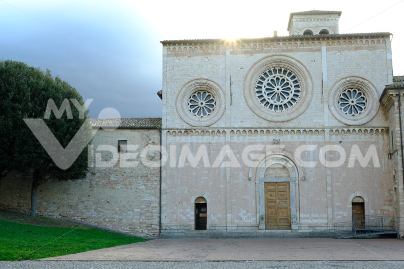 Church of San Pietro in Assisi with the stone wall. Romanesque church with a façade with three light-colored rose windows. - MyVideoimage.com