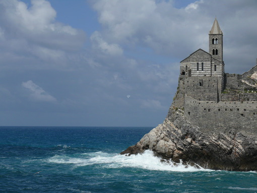 Church of San Pietro in Portovenere, built on a rock overlooking the sea. Sky with clouds and blue sea waves. - MyVideoimage.com