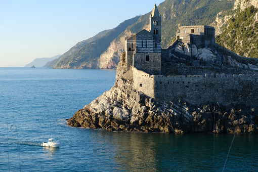 Church of San Pietro in Portovenere on the rocks overlooking the sea. White boat in the sea and rocks near the Cinque Terre in Liguri. Italy. - LEphotoart.com