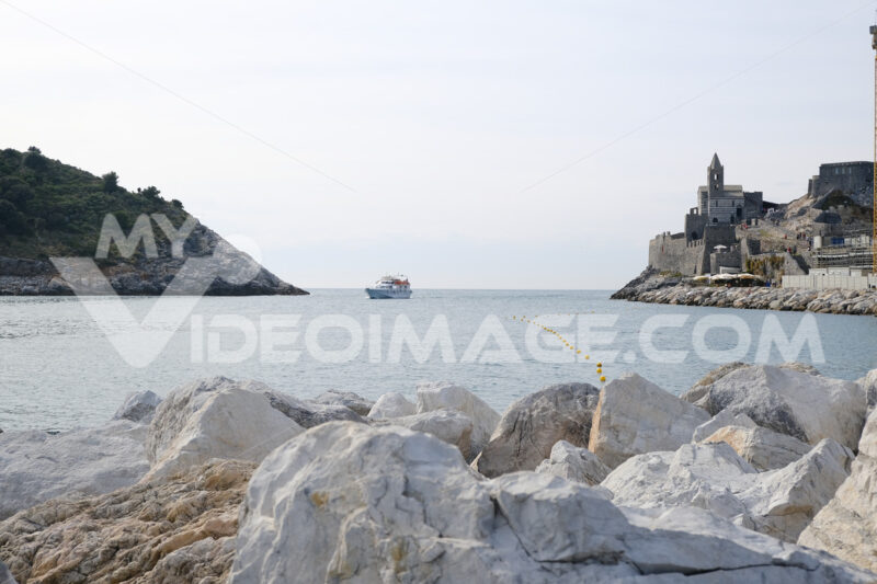 Church of San Pietro in Portovenere overlooking the sea. Boats with tourists visiting the Cinque Terre. - MyVideoimage.com