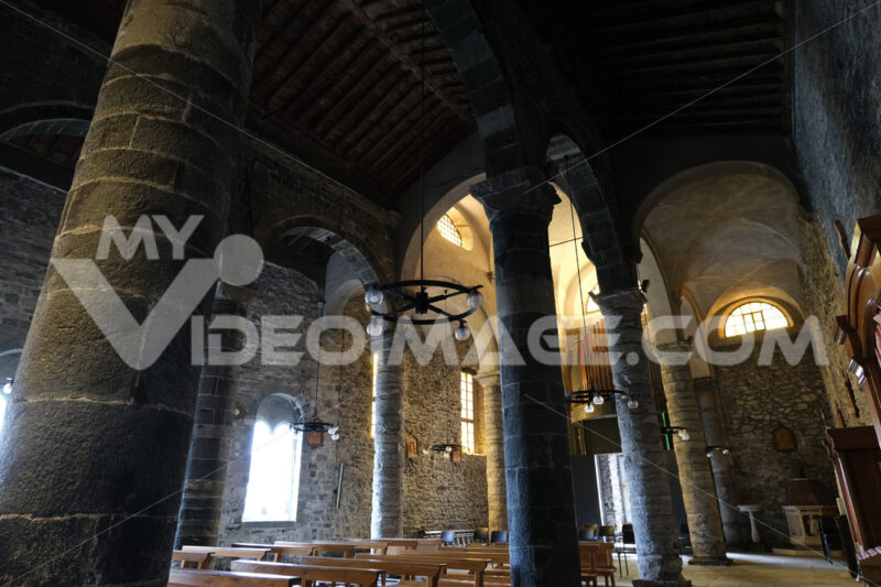 Church of Santa Margherita di Antiochia. Interior with columns and stone walls in Romanesque style. Città italiane. Italian cities.