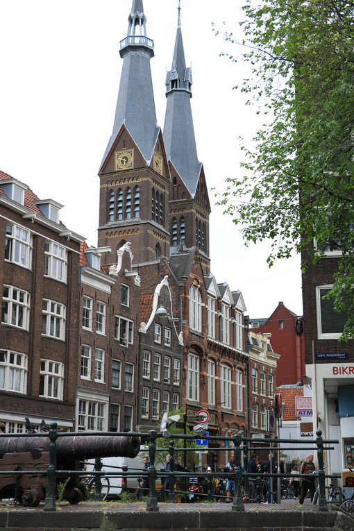 Church towers in the center of Amsterdam. In the foreground, a bridge over a canal with an old cannon. - MyVideoimage.com