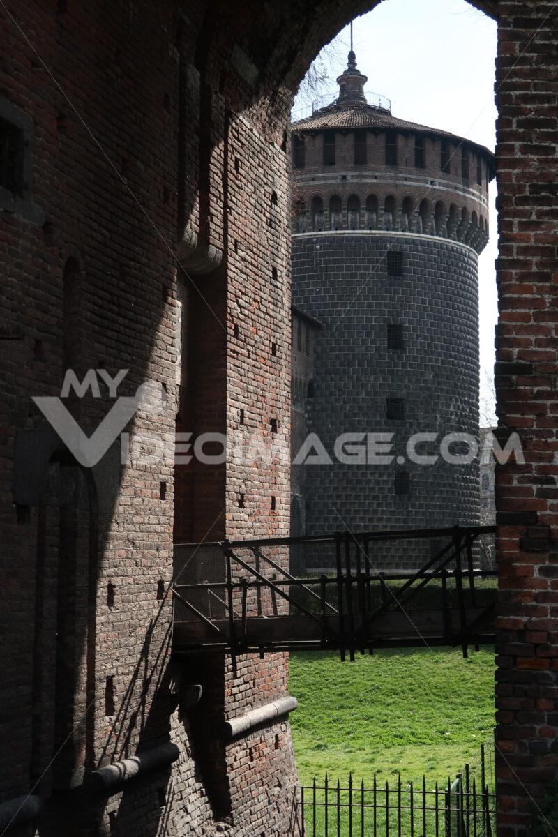 Circular brick tower of the Sforzesco Castle in Milan. Iron bridge and green lawn. MIlano foto. - MyVideoimage.com