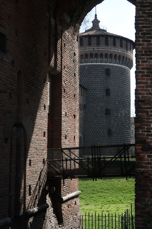 Circular brick tower of the Sforzesco Castle in Milan. Iron bridge and green lawn. MIlano foto. - MyVideoimage.com