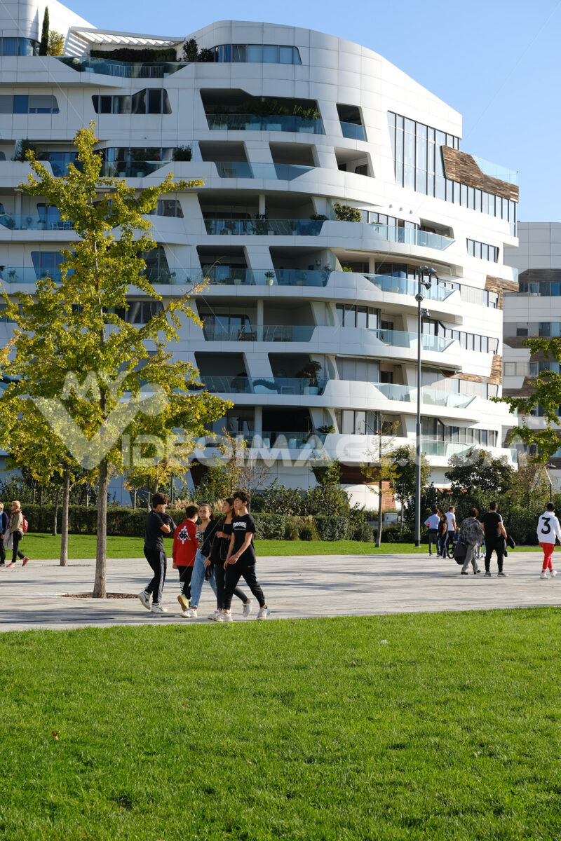 CityLife Milan Residential Complex. Palaces designed by Zaha Hadid. People stroll in the green gardens. - MyVideoimage.com