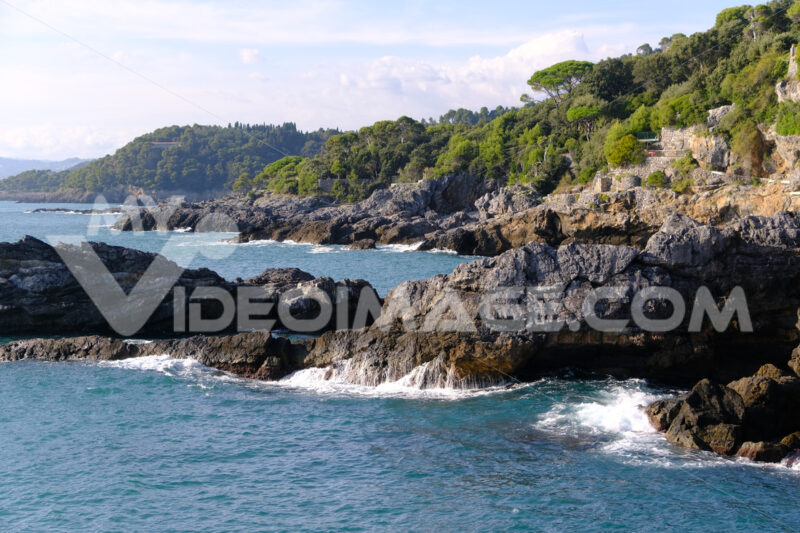 Cliff by the sea in the village of Tellaro di Lerici, near the Cinque Terre. Waves of the blue sea break on the rocks. Province of La Spezia. - LEphotoart.com