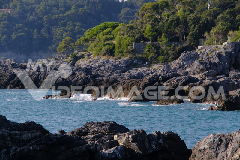 Cliff by the sea in the village of Tellaro di Lerici, near the Cinque Terre. Waves of the blue sea break on the rocks. Province of La Spezia. - MyVideoimage.com