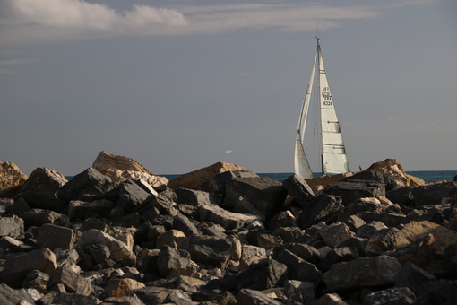 Cliff by the sea with a view of a sailboat. - MyVideoimage.com