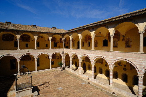 Cloister with columns and arches at the Basilica of San Francesco in Assisi. In the center of the courtyard there is a well in beige stone. - MyVideoimage.com
