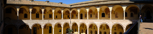 Cloister with columns and arches at the Basilica of San Francesco in Assisi. In the center of the courtyard there is a well in beige stone. - LEphotoart.com