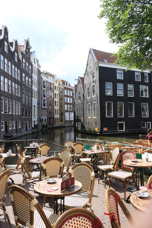 Coffee on a canal. Wooden tables and chairs in the bar. On the t - MyVideoimage.com