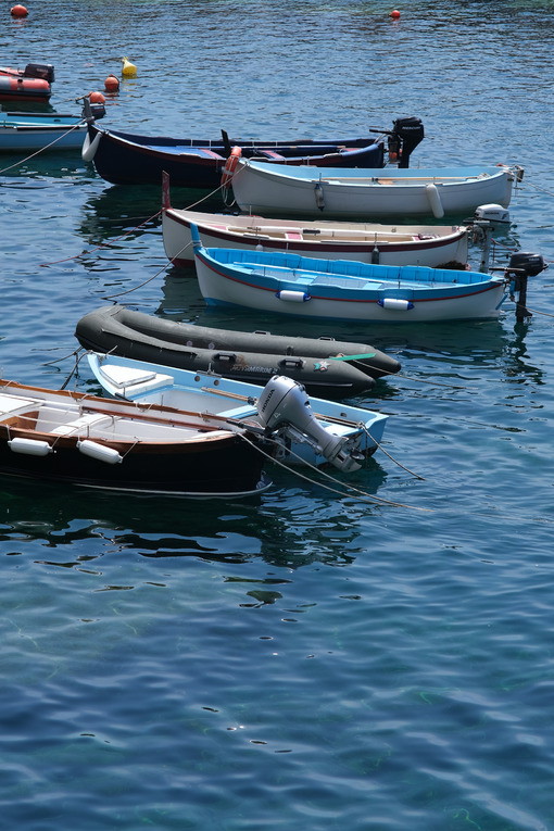 Colored boats on the blue sea. Riomaggiore, Cinque Terre. Stock Photos. - MyVideimage.com