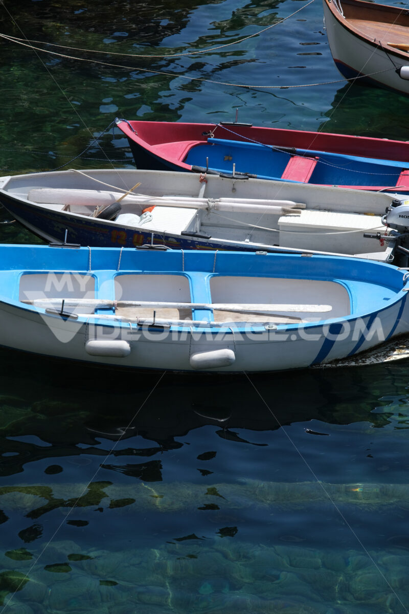 Colored boats on the blue sea. Riomaggiore, Cinque Terre. Stock Photos. - MyVideoimage.com