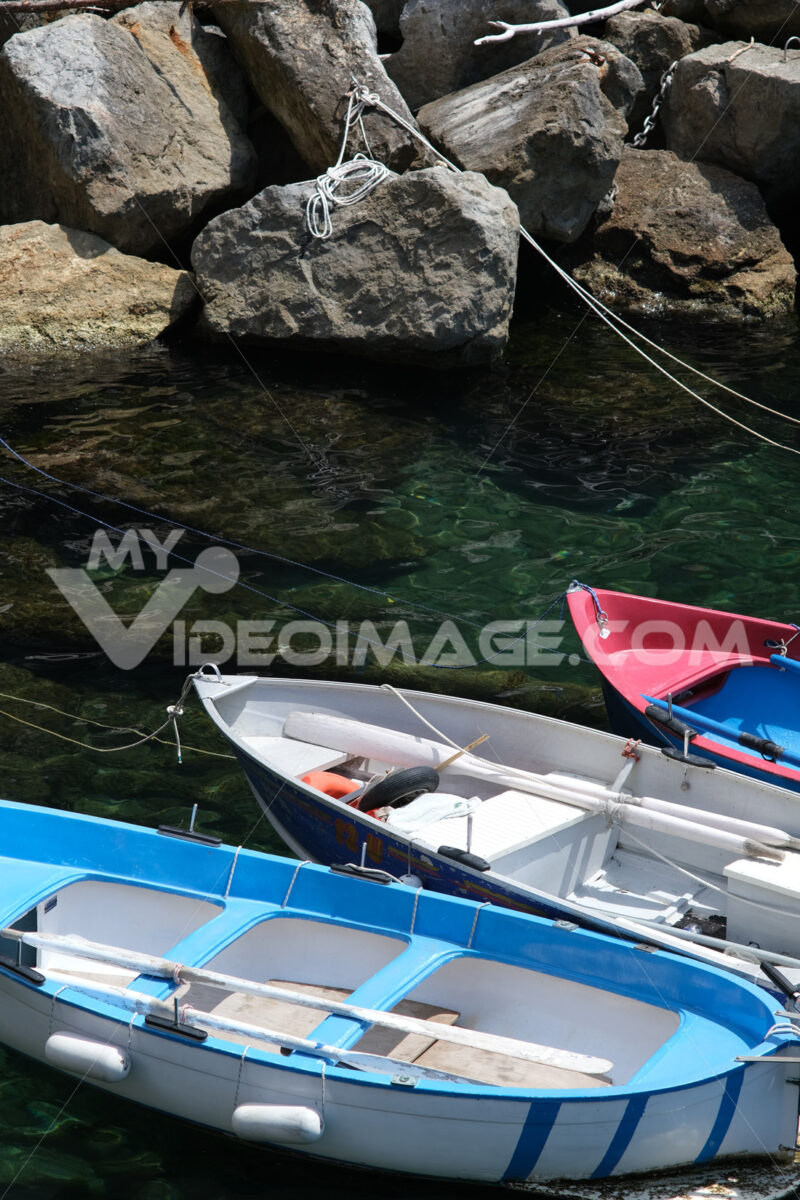 Colored boats on the blue sea. Riomaggiore, Cinque Terre. Stock Photos. - LEphotoart.com