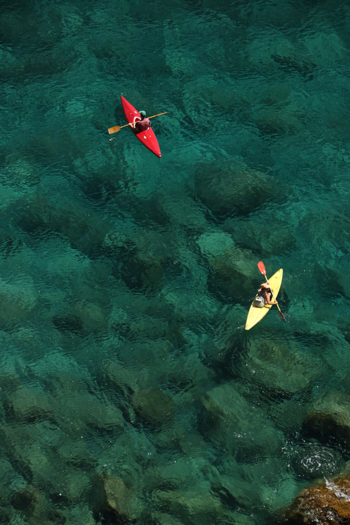 Colorful canoe on the transparent sea of the Cinque Terre. Top view with sea bottom with rocks and pebbles. - MyVideimage.com