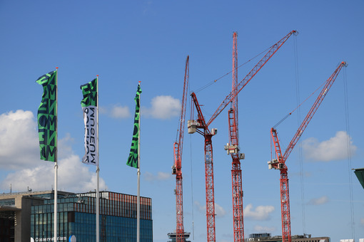 Construction crane in the city center. Blue sky background. Museum flags and conservatory building. - LEphotoart.com