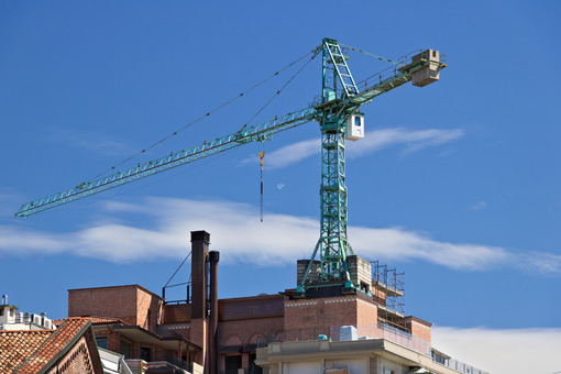 Construction crane mounted on the roof of a building in Milan. Cantieri edili. - LEphotoart.com